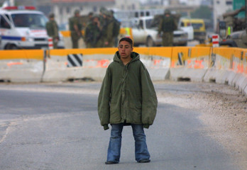 A PALESTINIAN BOY WHO WAS CAUGHT WITH AN EXPLOSIVE BELT STANDS AT THE CHECKPOINT INTO NABLUS.