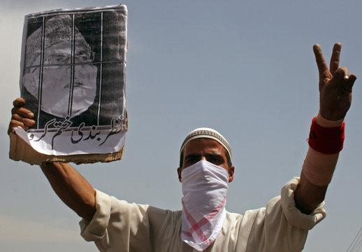 Masked demonstrator, holding picture of Kashmiri senior hardliner separatist leader, gestures during protest march in Srinagar