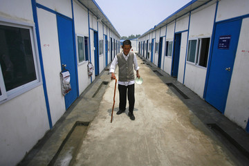 A survivor of the earthquake walks past newly constructed temporary housing in Sichuan province