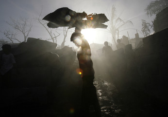 A resident carries charred roofing materials after a fire in Mandaluyong City, Metro Manila