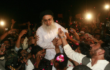 Supporters shower rose petals on Aziz, a radical Pakistani cleric and the former chief cleric of the Red Mosque, as he arrives at the Red Mosque after his release from house arrest in Islamabad