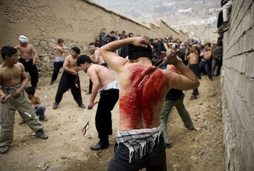 Afghan Shi'ite Muslims flagellate themselves with chains during an Ashura procession in Kabul