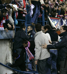 Supporters lie on the floor after a barrier collapsed during a Spanish First Division match in Madrid
