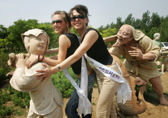 Miss Tourism Queen International contestants from Germany and Macedonia pose next to a Chinese ...