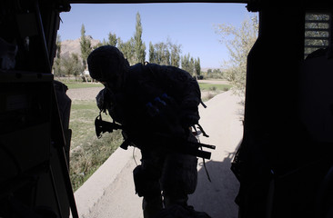 Soldier from the U.S. Army climb up to his armored vehicle during a joint patrol with Afghan soldiers