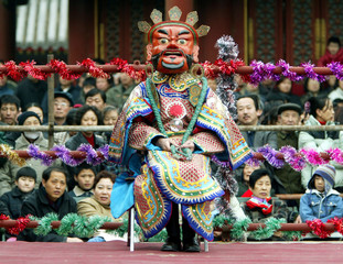 A Tibetan monk wears a traditional mask during a ceremony to celebrate the Tibetan New Year at Beiji..