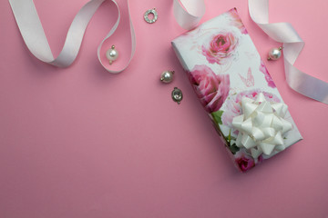 Pink background with wrapped gift, white satin ribbon and pearl and crystal charms for Mothers day or birthday