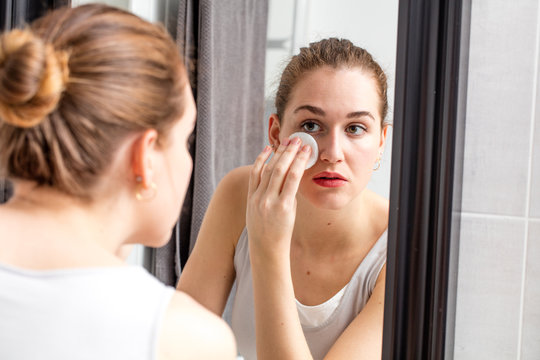 young woman removing makeup with swab in front of mirror