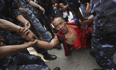 Police drag a Tibetan monk during a pro-Tibet demonstration in Kathmandu