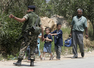 A Palestinian man arrives with his children at a Lebanese army checkpoint outside Nahr al-Bared refugee camp in northern Lebanon