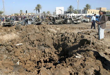 IRAQI MAN LOOKS AT A CRATER MADE BY A CAR BOMB OUTSIDE A POLICE STATIONAFTER AN ATTACK IN BAQUBA.