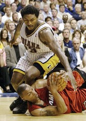 HEATS CARON BUTLER FIGHTS FOR LOOSE BALL WITH PACERS RON ARTEST.