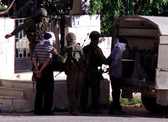 A ISRAELI SOLDIER IS AIMING TO HIT AN ARRESTED PALESTINIAN MAN INADDUHA AREA IN BETHLEHEM.