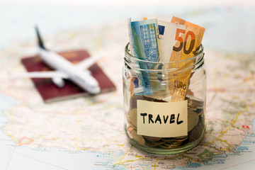 travel budget concept, money savings in a glass jar on a map