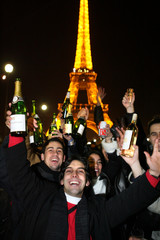 Revellers celebrate the New Year at the foot of the Eiffel tower in Paris