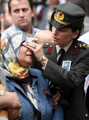 A Turkish officer wipes tears from the face of Hanife, the mother of paramilitary police Emrah Kayadelen, during his funeral ceremony in Istanbul
