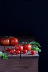 Помидоры,томаты,листья салата на деревянном столе,тёмный фон