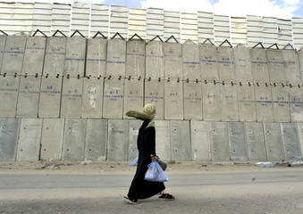 A PALESTINIAN WOMAN PASSES IN FRONT OF THE NEVE DEKALIM JEWISHSETTLEMENT.