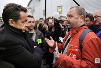 France's President Sarkozy speaks with a CGT trade union representative during a visit to a depot of the state train operator SNCF in Saint-Denis