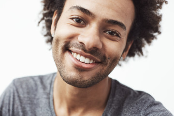 Close up portrait of handsome cheerful african man smiling looking at camera. White background.
