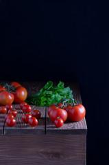 Помидоры,листья салата на деревянном столе