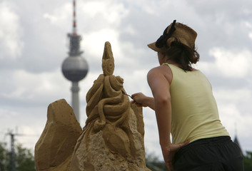 An artist works on a sand sculpture at the fifth international sand sculptures festival 'Sandsation' in Berlin