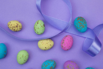 Lilac background with speckled pink, green, yellow and blue coloured sweet eggs and purple satin ribbon - Easter