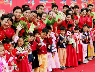 Chinese couples pose with South Korean children during their mass wedding ceremony in Yongin