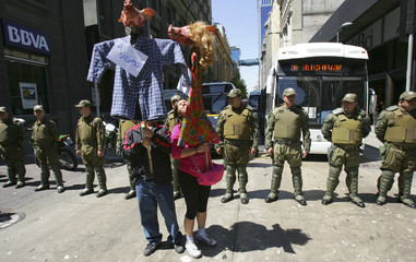 Demonstrators hold up pig heads as riot policemen stand guard during a rally in downtown Santiago