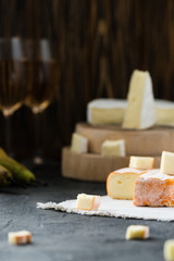 French soft cheese from Brittany region and brie sliced, with pear, glasses of white wine on dark rustic background