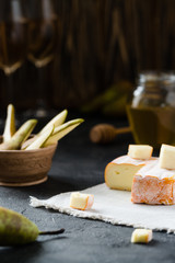 French soft cheese from Brittany region and sliced brie with pear, honey and glasses of white wine on dark rustic background