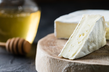 Closeup of soft cheese brie sliced on wooden cut with honey and spoon on dark rustic background