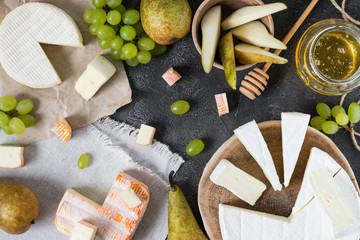 Platter of French soft cheeses from Normandy and Brittany regions, and brie sliced with honey, pear and green grapes on dark rustic background, top view