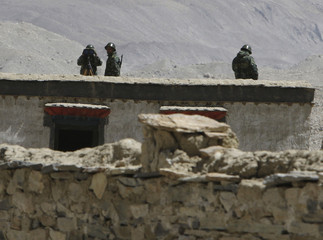 Chinese security personnel watch from their observation post in front of peak of Mount Everest