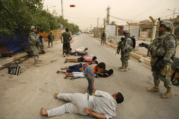 A U.S. soldier throws a bottle of drink to a fellow soldier during a joint military operation with the Iraqi army in Baghdad's Sadr City