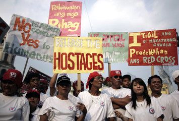 Participants hold placards calling for the release of abducted ICRC members during a rally in Manila