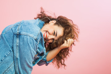 Beautiful young woman with curly hair in denim clothes