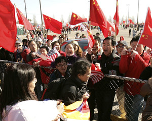 A man carries a Tibetan flag past demonstrators with Chinese flags before the start of the Olympic Torch relay in San Francisco