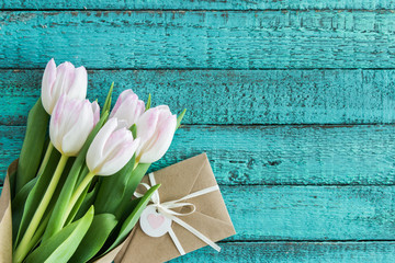 light pink tulips bouquet and envelope on turquoise wooden tabletop with copy space, wedding cards flowers concept