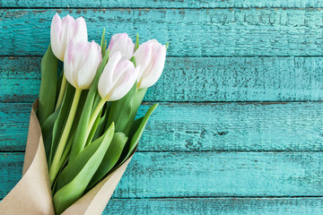 light pink tulips bouquet on turquoise wooden tabletop with copy space, wedding flowers background concept