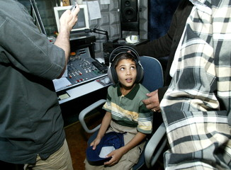 - PHOTO TAKEN 03JUL04 - An Iraqi boy from Hilla tests headphones at a radio station during his stay ..