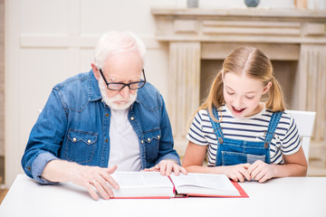 Smiling girl and grandfather in eyeglasses reading book together at home