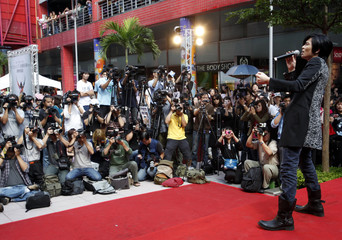 Cameramen and photographers surround Taiwan singer Jam Hsiao as he performs in Taipei
