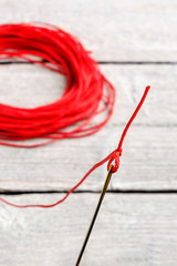 needle with red thread, focus on the eye of a needle, on white wooden background