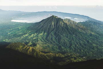 View of Batur Caldera and Gunung Abang from mount Agung in Bali at sunrise summit. Top of Agung Volcano. Agung trekking and hiking.