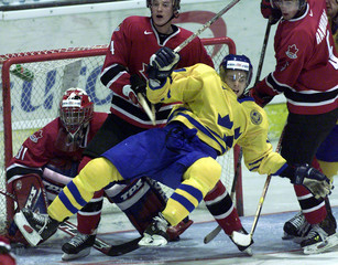 MARTIN SAMUELSON IS TACKLED IN FRONT OF CANADIAN GOALIE.