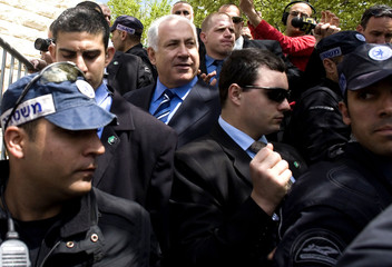 Likud party leader Netanyahu is surrounded by police officers after leaving a polling station in Jerusalem