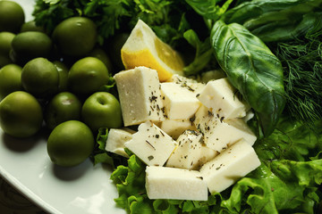 Olives, brynza and greens on a plate,Fresh salad with bryndza, olives,plate of soft cheese (feta and bryndza),Green olives in the bowl