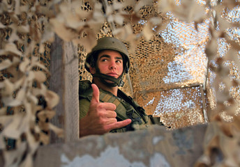 Israeli soldier stands guard at military checkpoint in Hebron