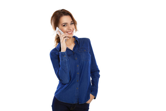 Happy look. Confident young girl in shirt talking on phone and looking at camera standing in front of white background
